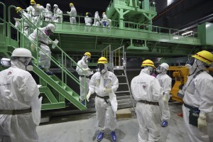 Members of the media and Tokyo Electric Power Co. employees wearing protective suits and masks walk down the steps of a fuel handling machine after looking at the spent fuel pool inside the building housing the Unit 4 reactor at the Fukushima Dai-ichi nuclear power plant in Okuma, Fukushima Prefecture, Japan, Thursday, Nov. 7, 2013. Japanese regulators on Oct. 30 formally approved the removal of fuel rods from the cooling pool at the damaged Unit 4 reactor building considered the highest risk at the crippled nuclear plant. Removing the fuel rods is the first major step in a decommissioning process that is expected to last decades at the Fukushima plant, where three reactors melted down after the March 2011 earthquake and tsunami. (AP Photo/Tomohiro Ohsumi, Pool)